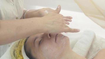 cosmetologista passa muitos cremes hidratantes no rosto de uma mulher em um salão de beleza