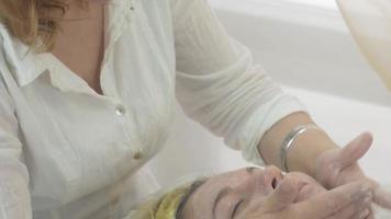 cosmetologista colocar creme hidratante no rosto da mulher no salão de beleza. cuidados com a pele