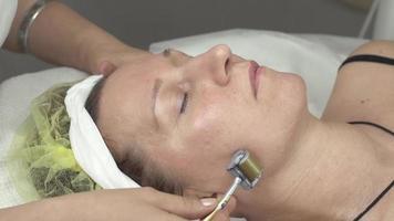 cosmetóloga hacer galvanoterapia rostro de mujer por rodillo en salón de belleza
