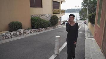 mulher adulta atraente andando na calçada falando no smartphone