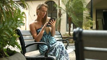 4k, junge, schöne Frau, die ebook liest, das auf Bank in der Stadt sitzt