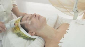 cosmetologista usar darsonval no rosto de mulher em salão de beleza. creme hidratante