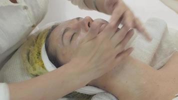 Kosmetikerin reiben Feuchtigkeitscreme im Gesicht der Frau im Schönheitssalon. Hautpflege