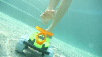 Frau stolpert über Spielzeug, das auf dem Boden eines Pools geht