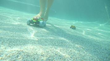 donna inciampa su giocattoli che camminano sul fondo di una piscina