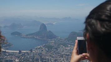 mulher tirando fotos com celular do corcovado no rio de janeiro