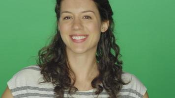 Young woman smiling and then wiggling her finger, on a green screen studio background video