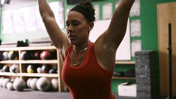 una giovane donna in forma che solleva un bilanciere e fa squat in una piccola palestra
