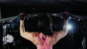 Attractive fitness woman pulls on the bar in the gym. Female bodybuilding. Bacl view video