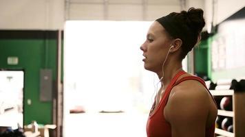 eine fitte junge Frau, die Hanteln hebt und Musik in einem kleinen Fitnessstudio hört