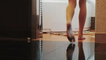 Ansicht der Frau, die zum Badezimmer geht und sich auf Bad setzt. sexy nackte Beine. Schritte