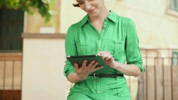 attraente giovane donna in abito estivo leggero utilizzando computer tablet per le strade della città europea.