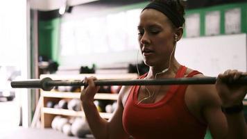 eine fitte junge Frau, die eine Langhantel in einem kleinen Fitnessstudio anhebt, während sie Musik hört