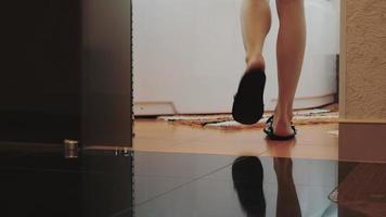 Vue de la jeune femme en pantoufles drôles à pied de la salle de bain et s'asseoir sur la baignoire