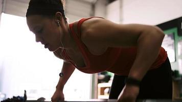 una giovane donna in forma che solleva un bilanciere in una piccola palestra mentre ascolta la musica