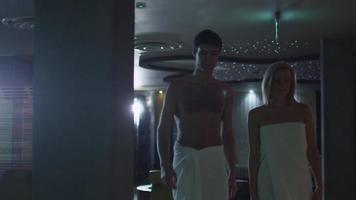 junger Mann und Frau gehen in Handtüchern in einem Wellnesscenter am Pool entlang.
