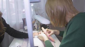 Maniküristenfeile unten obere Abdeckung von den Nägeln der Frau durch Nagelfeile. Schellackentfernung. Verwenden Sie Puderquaste