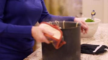 uma mulher movendo uma panela de espaguete quente para um balcão com suportes para panelas e sorrindo
