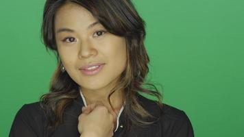 Young Asian woman smiling and putting her hair behind her hair, on a green screen studio background video