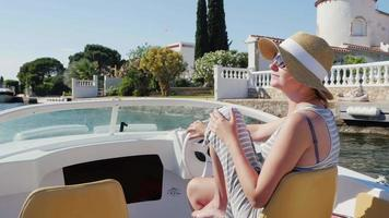 Holiday dreams in Europe. Woman in sunglasses and hat floating in a small boat in Empuriabrava, Spain video