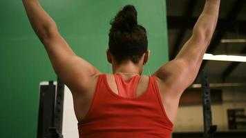 una giovane donna in forma che solleva un bilanciere e fa squat in una piccola palestra, vista da dietro