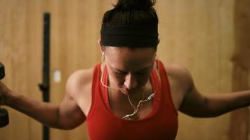 Nahaufnahme einer fitten jungen Frau, die Hanteln hebt und Musik in einem kleinen Fitnessstudio hört