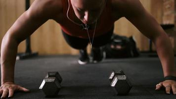 Nahaufnahme einer fitten jungen Frau, die Liegestütze macht und Musik in einem kleinen Fitnessstudio hört