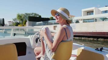 junge Frau, die einen Urlaub auf dem europäischen Ferienort genießt. schwimmend auf einem Boot auf dem Kanal Empuriabrava, Spanien video