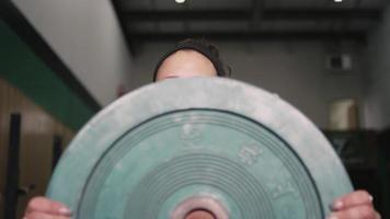 una giovane donna in forma che lavora con una piastra paraurti in una piccola palestra mentre si ascolta la musica