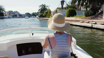 Young woman tourist rides on a motor boat on the canal. Empuriabrava, Spain. Concept: vacation in Europe, sea tour video