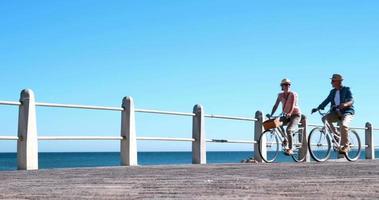personnes âgées actives faisant une balade à vélo au bord de la mer
