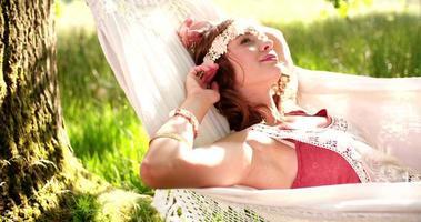 Chica hippie relajándose en una hamaca en un parque iluminado por el sol video