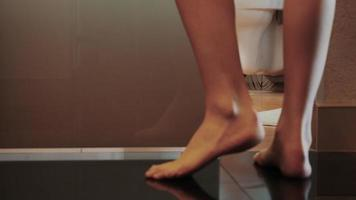 jeune fille marche vers la salle de bain, porte ouverte vient évier. petits tapis. jambes nues
