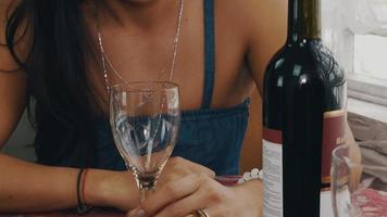 garota conversando à mesa com a garrafa no terraço da casa de campo. copo vazio