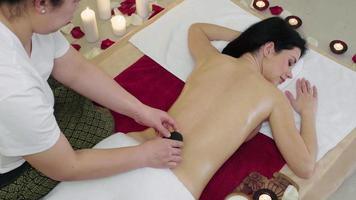 belle jeune fille brune ayant un massage aux pierres