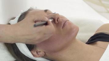 Nahaufnahme von Kosmetikerhänden setzen Feuchtigkeitscreme auf Mädchengesicht im Schönheitssalon