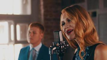 Attractive jazz vocalist perform on stage with saxophonist in blue suit. Music video