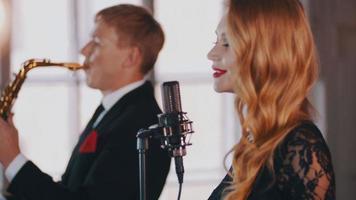 cantante femminile attraente cantare sul palco, ballare. sassofonista. duetto jazz video