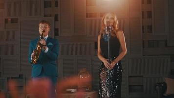 Chanteur de jazz en robe d'éblouissement danse chanter sur scène avec le saxophoniste en costume bleu
