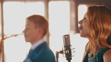danza cantante jazz attraente esibirsi sul palco con il sassofonista in abito blu video