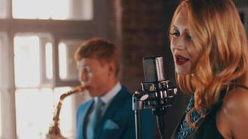 cantante jazz attraente con labbra rosse esibendosi sul palco con il sassofonista