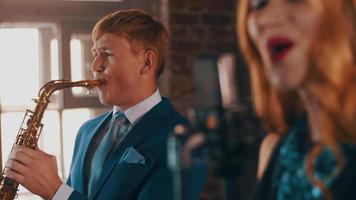cantante jazz attraente che si esibisce sul palco con il sassofonista in abito blu. vivere video