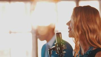 cantante jazz attraente danza cantare sul palco con il sassofonista in abito blu video