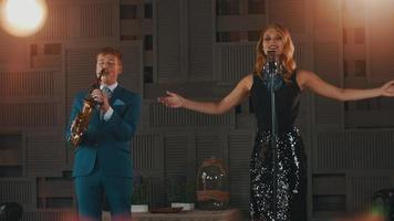 chanteur de jazz en robe éblouissante et saxophoniste en costume bleu sur scène. duo
