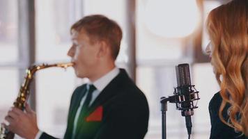 jolie chanteuse sur scène, danse. jeu de saxophoniste. duo de jazz