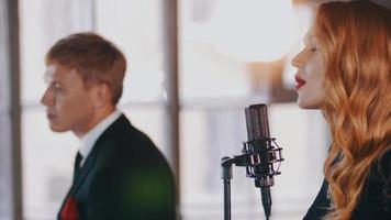 cantante femminile attraente cantare sul palco, ballare. il sassofonista si esibisce. duetto jazz