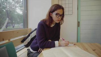 bella ragazza seduta al tavolo studiando e scrivendo in taccuino