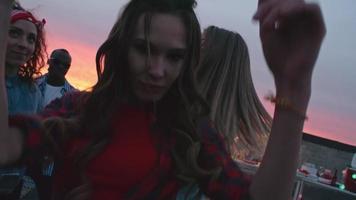 garota sexy dançando com amigos no telhado