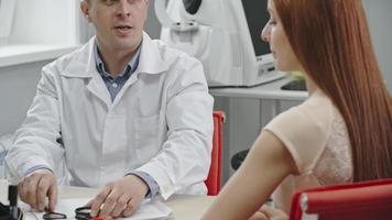 Optometrista revisando los ojos de la paciente video