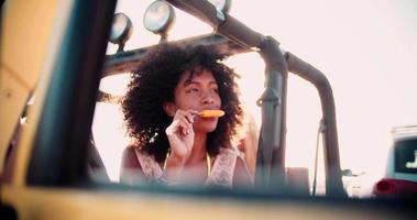 ragazza afro-americana che mangia ghiaccioli in auto